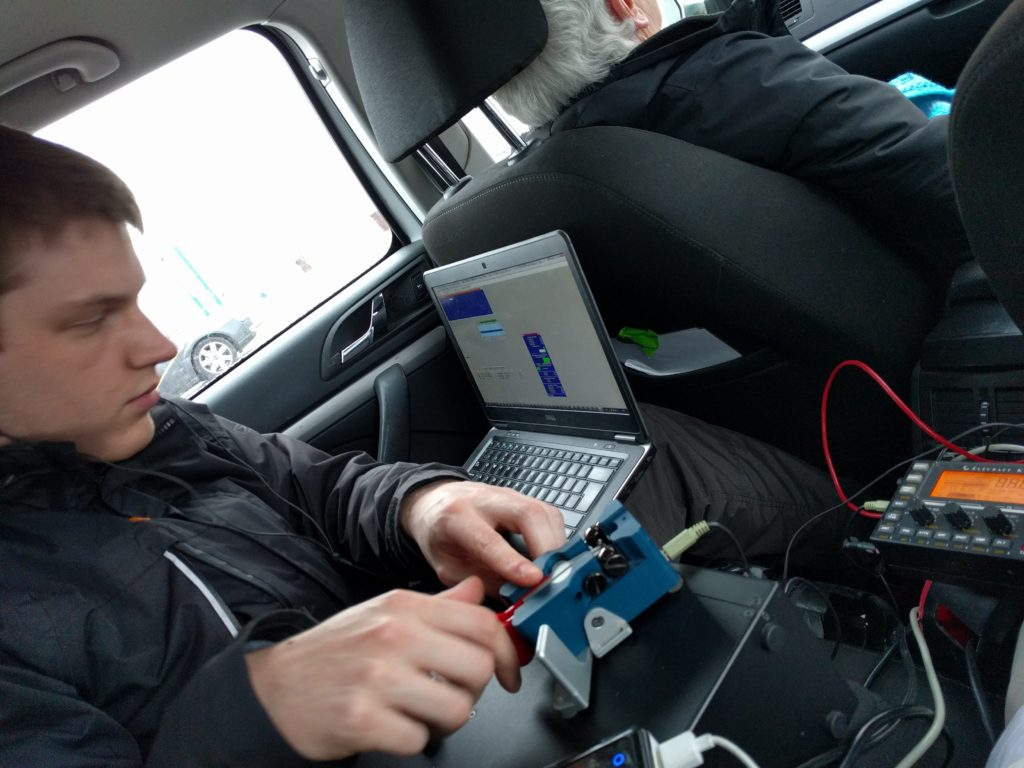Dan cramped on the back seat of a car with Morse paddle and laptop