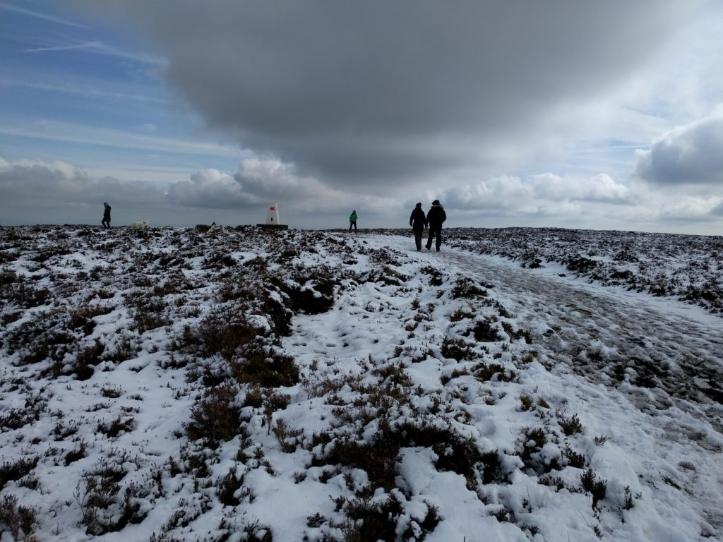 People walking on path with a thin layer of snow and trig point in the distance