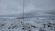 Fibreglass antenna mast standing on snowy ground