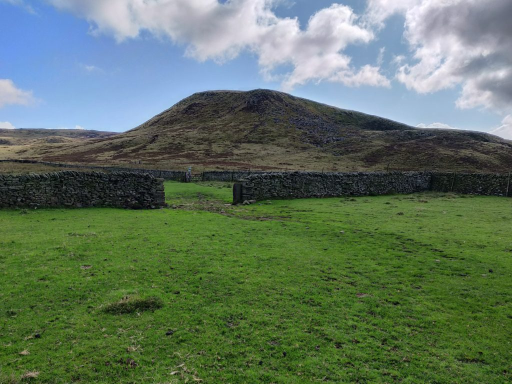 Field with gap in wall and hill behind