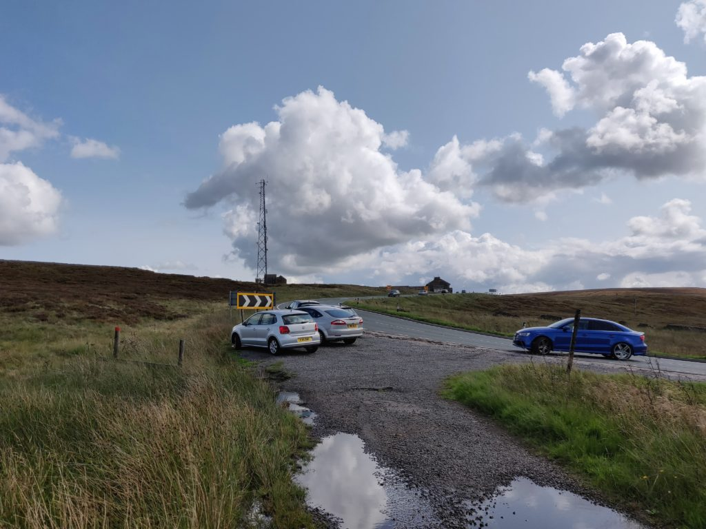 Cars parked in gravel layby off road surrounded by moorland