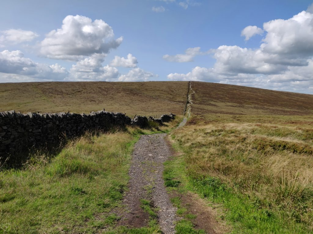 Gravel walking path uphill surrounded by moorland