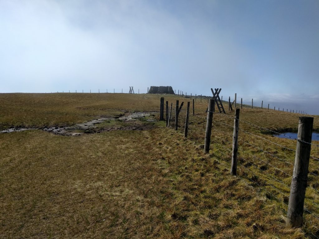 Fence over grassland with stone shelter