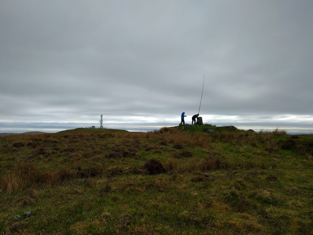 Fibreglass pole at the trig point, with the transmitter site in the background