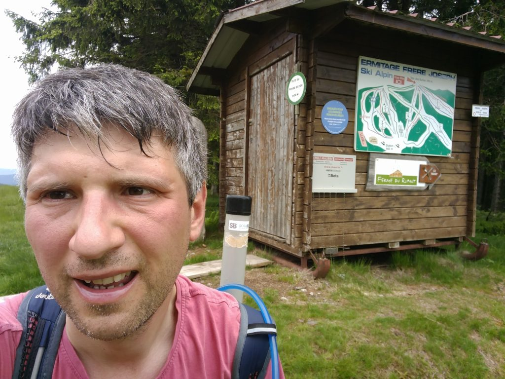 Me by a wooden shelter with signs