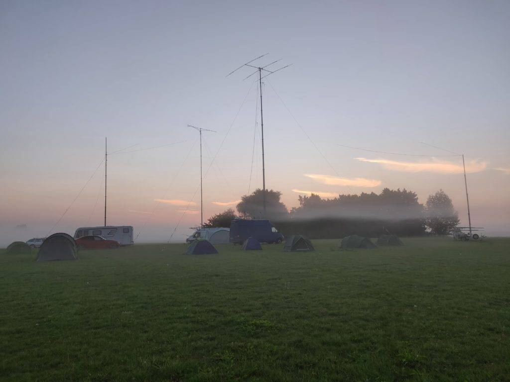 Mist hanging over a field with tents